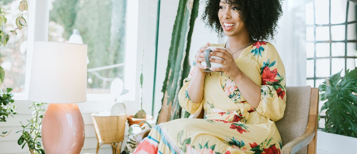 Woman in floral print dress drinking coffee in a well-lit living room.